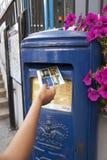 Mano che mette una cartolina in un contenitore blu di posta di Guernsey unico a Guernsey nella citt? della st Pierre Port St Pete fotografie stock