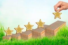 Mano che mette una forma di legno di cinque stelle sulla tavola I migliori servizi commerciali eccellenti che valutano concetto d fotografia stock libera da diritti
