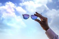 Mano che mostra cielo attraverso i sunglass Fotografia Stock Libera da Diritti