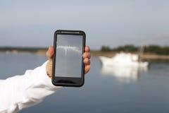 Mano che mostra telefono cellulare astuto con lo schermo in bianco Fotografie Stock Libere da Diritti