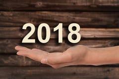 Mano che offre 2018 numeri, fondo di legno Fotografie Stock