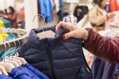 Mano che rovista nel negozio di vestiti, concetto della donna di consumismo immagine stock libera da diritti