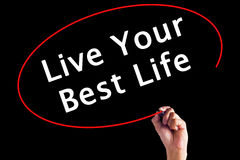 Mano che scrive Live Your Best Life con un indicatore fotografie stock