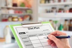 Mano che scrive un programma di dieta davanti ad un frigorifero Fotografia Stock Libera da Diritti