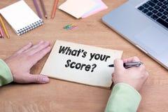 Mano che scrive What& x27; s il vostro punteggio? Scrivania con un computer portatile e una st fotografia stock