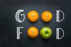 Mano che segna buon alimento con lettere sulla lavagna nera con le arance Apple verde di frutti Energia pulita sana delle vitamin immagini stock