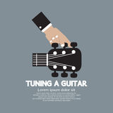 Mano che sintonizza una chitarra Fotografia Stock