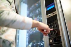 Mano che spinge bottone sulla tastiera del distributore automatico Immagine Stock