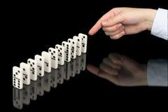 Mano che spinge i contatori di domino sul nero Fotografie Stock