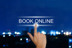 Mano che spinge il bottone online del libro sul touch screen fotografia stock
