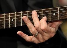 Mano che strumming le stringhe della chitarra immagini stock libere da diritti