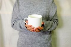 Mano che tiene bevanda calda con il maglione grigio Fotografie Stock Libere da Diritti