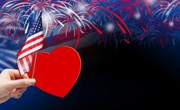 Mano che tiene cuore e la bandiera di carta rossi di U.S.A. con i fuochi d'artificio Immagine Stock Libera da Diritti