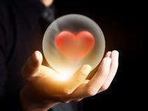 Mano che tiene cuore rosso in sfera di cristallo Immagine Stock