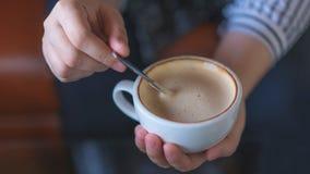 Mano che tiene e che mescola caffè caldo immagine stock
