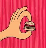 Mano che tiene hamburger minuscolo Fotografia Stock Libera da Diritti