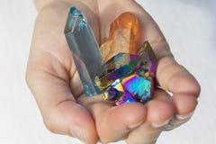 Mano che tiene i vari cristalli di aura immagini stock