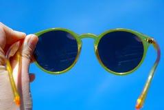 Mano che tiene i vetri di Sun gialli sopra la copia blu Sapce del cielo di estate per testo Fotografie Stock Libere da Diritti