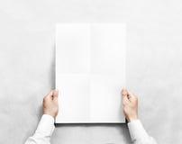 Mano che tiene il modello in bianco bianco del manifesto, Immagine Stock