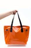 Mano che tiene la borsa arancio delle donne Fotografia Stock