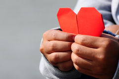 Mano che tiene la carta rossa del cuore Fotografia Stock