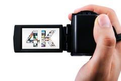 Mano che tiene la videocamera portatile ultra alta di definizione Immagini Stock Libere da Diritti
