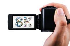 Mano che tiene la videocamera portatile ultra alta di definizione Fotografie Stock