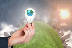 Mano che tiene lampadina ambientale Fotografie Stock Libere da Diritti