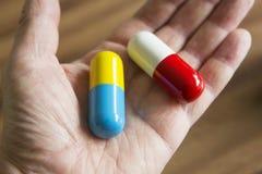 Mano che tiene le capsule surdimensionate del farmaco Immagine Stock