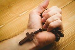 Mano che tiene le perle di legno del rosario Fotografie Stock Libere da Diritti
