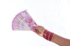Mano che tiene 2000 note della rupia contro il bianco Fotografie Stock