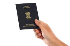 Mano che tiene passaporto indiano contro il fondo bianco Immagini Stock