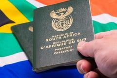 Mano che tiene passaporto sudafricano sulla bandiera del SA fotografia stock