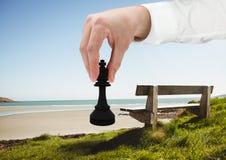 Mano che tiene pezzo degli scacchi dalla spiaggia Immagine Stock