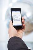 Mano che tiene Smartphone con il nuovo messaggio Fotografia Stock