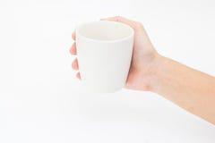 Mano che tiene tazza su un fondo bianco Fotografie Stock