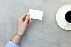 Mano che tiene un biglietto da visita in bianco con la tazza di caffè su fondo grigio fotografia stock libera da diritti