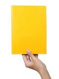 Mano che tiene un colore giallo del documento in bianco Immagine Stock Libera da Diritti