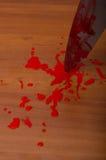 Mano che tiene un coltello sanguinoso Immagine Stock