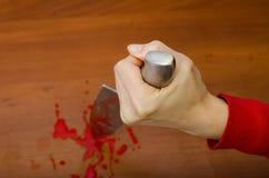 Mano che tiene un coltello sanguinoso Fotografie Stock