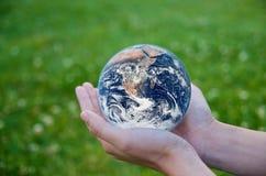 Mano che tiene un globo. Salvo l'ambiente della terra Immagine Stock