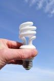 Mano che tiene un indicatore luminoso fluorescente compatto (CFL) Fotografia Stock