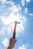 Mano che tiene un martello sul cielo del fondo Immagini Stock Libere da Diritti