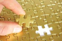 Mano che tiene un puzzle Fotografie Stock Libere da Diritti