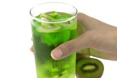 Mano che tiene un vetro del succo del kiwi Immagini Stock Libere da Diritti