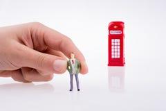 Mano che tiene una figura vicino ad una cabina telefonica Fotografia Stock