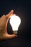 Mano che tiene una lampadina luminosa Fotografia Stock Libera da Diritti