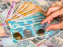 Mano che tiene una moneta da 5 rupie immagine stock