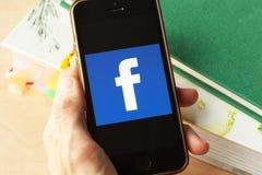 Mano che tiene uno smartphone con un'icona di Facebook sullo schermo fotografia stock libera da diritti