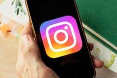 Mano che tiene uno smartphone con un'icona di Instagram sullo schermo fotografia stock